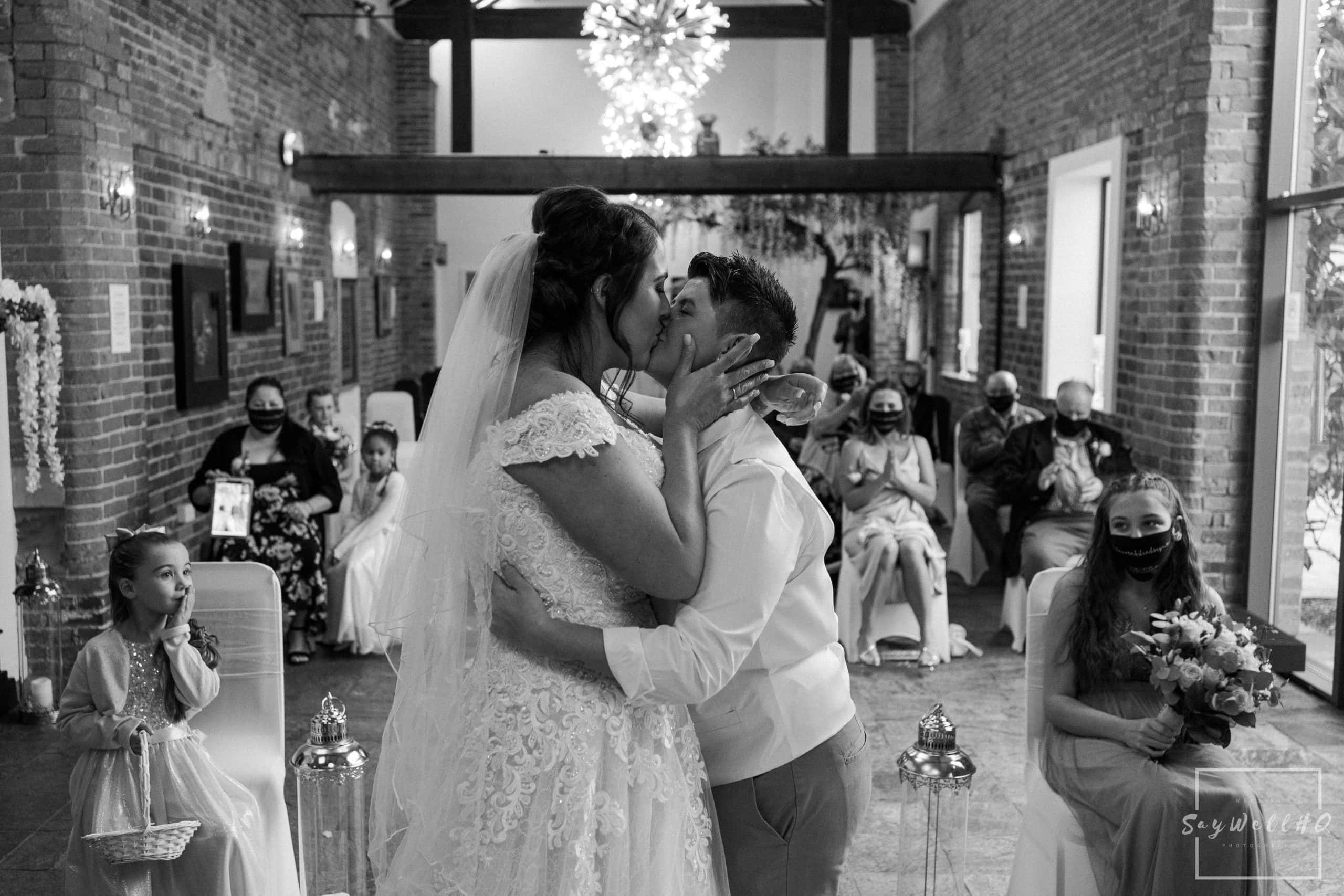 same sex couple kiss with their wedding guests looking on during their summer wedding ceremony at Goosedale - Wedding Photography by goosedale wedding photographer Andy Saywell of SaywellHQ