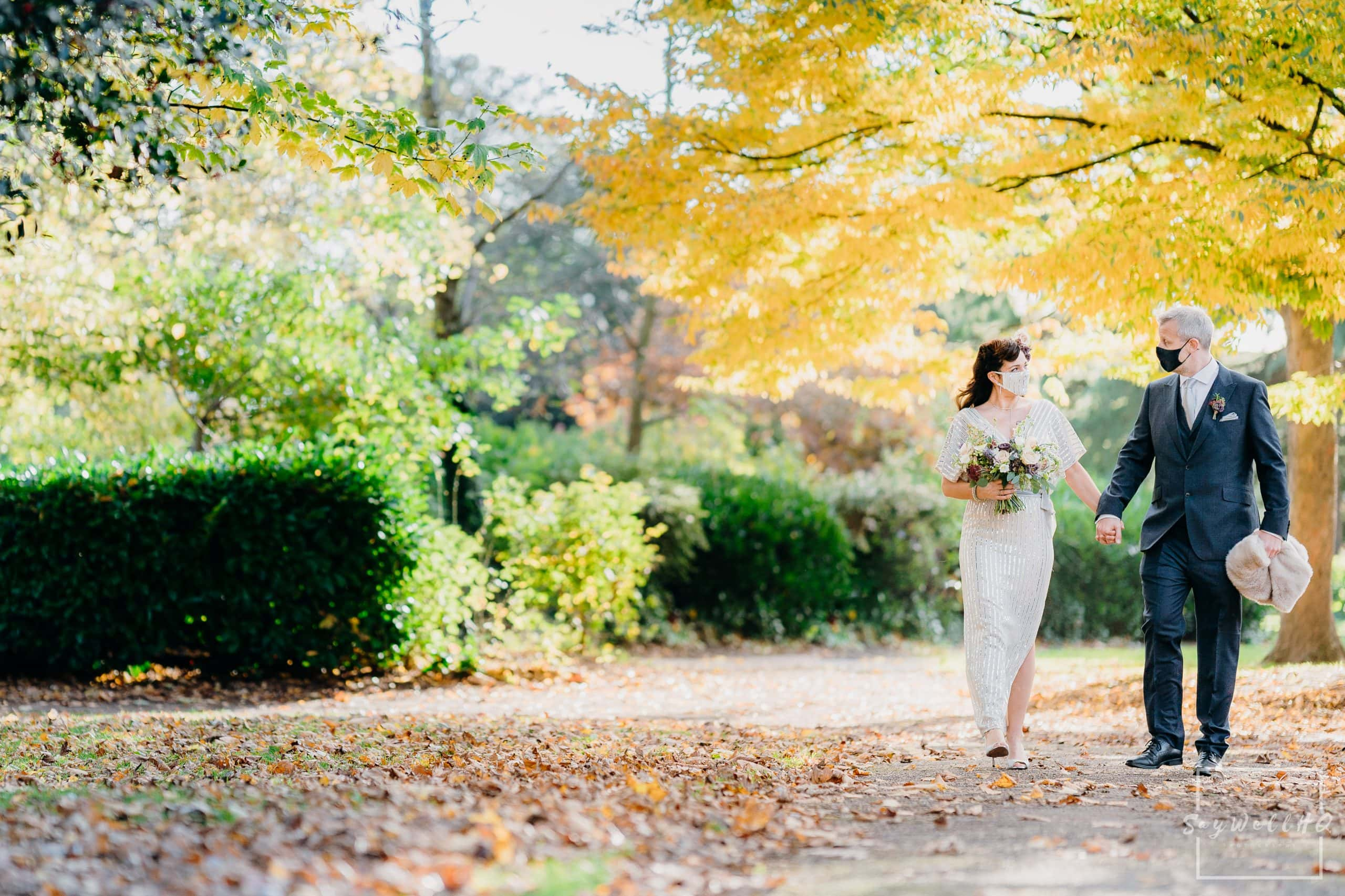 Bride and groom take a stroll through a park whilst wearing face masks following their covid wedding in 2020