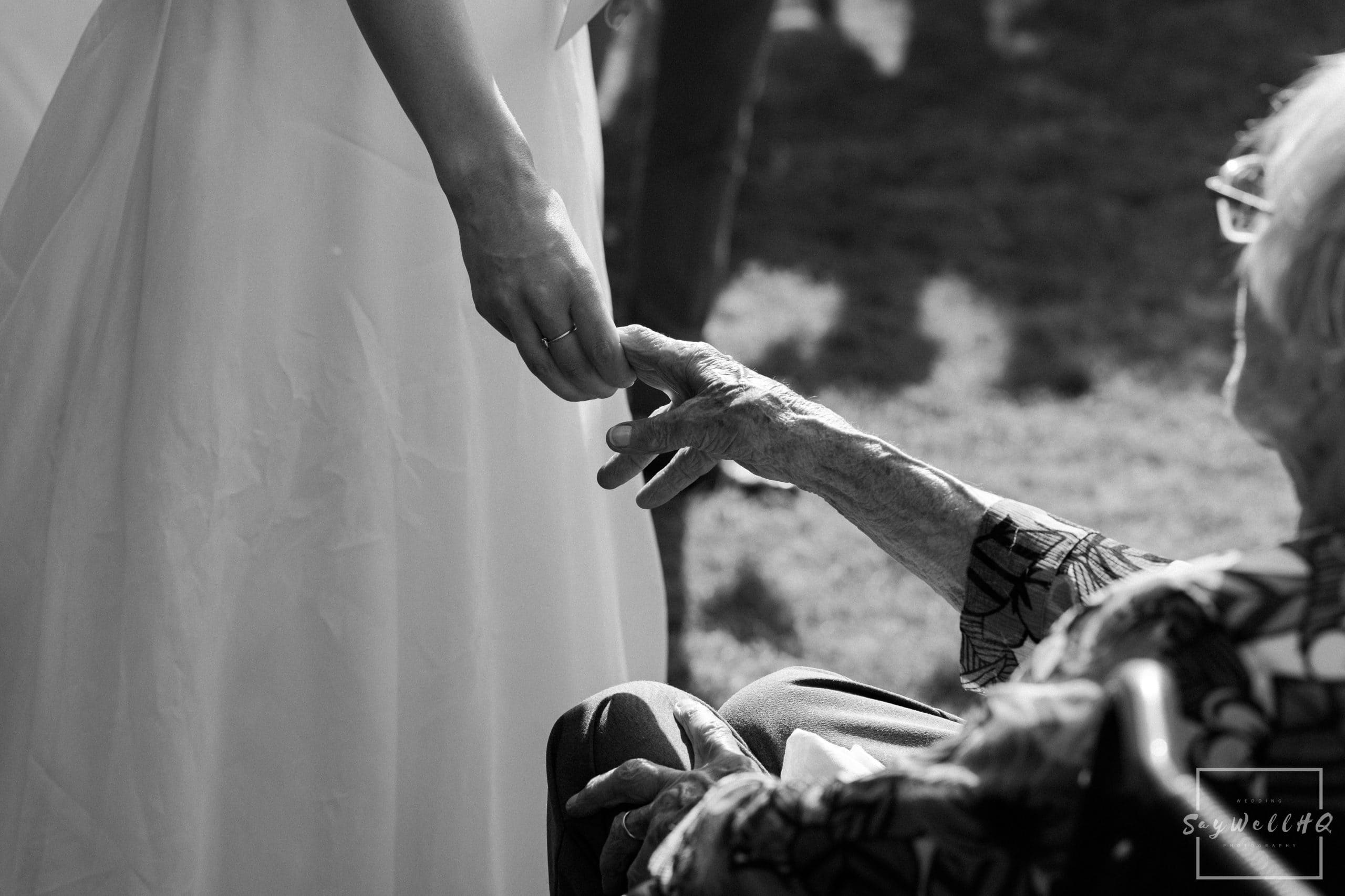The bride holding hands with her grandma during the wedding speeches at a micro church wedding in 2020