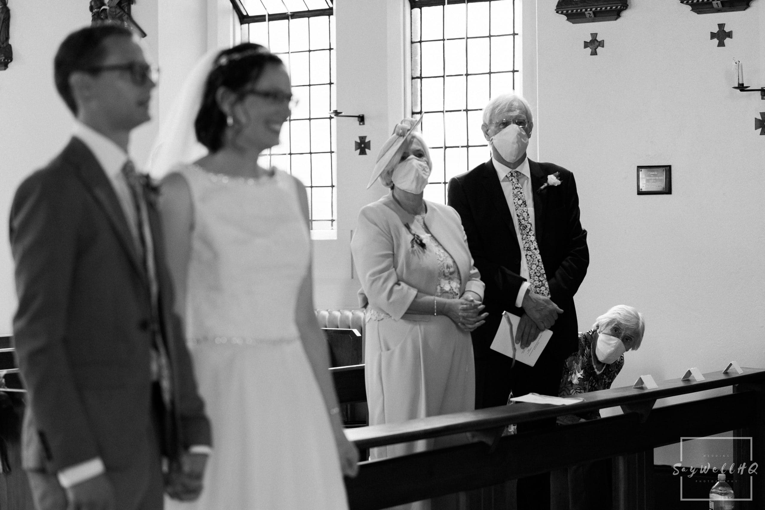 Grandma looking at her grand daughter getting married whilst wearing a facemask during the wedding ceremony