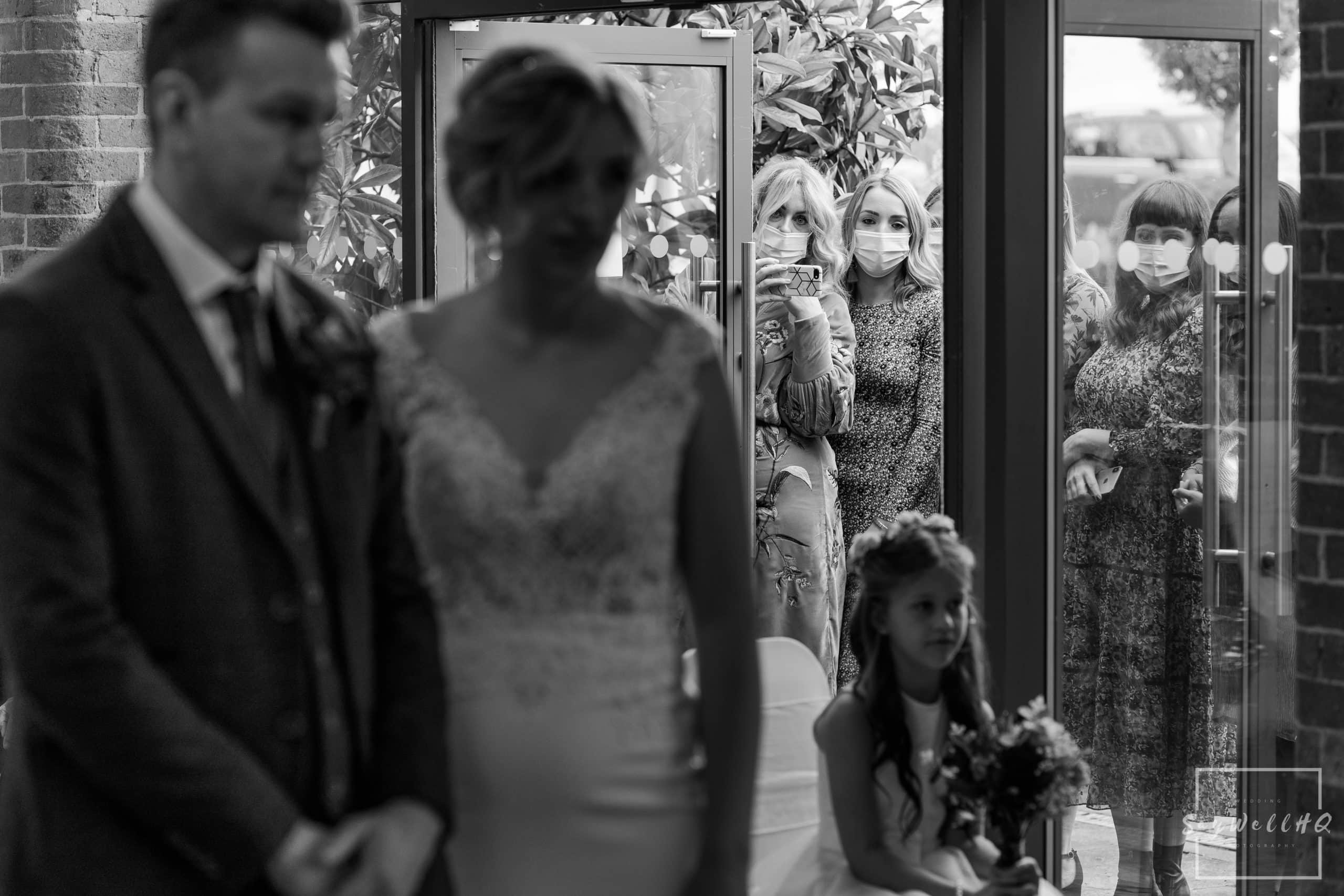 Friends of the bride watching the wedding ceremony through the outside doors due to the covid 19 wedding restrictions