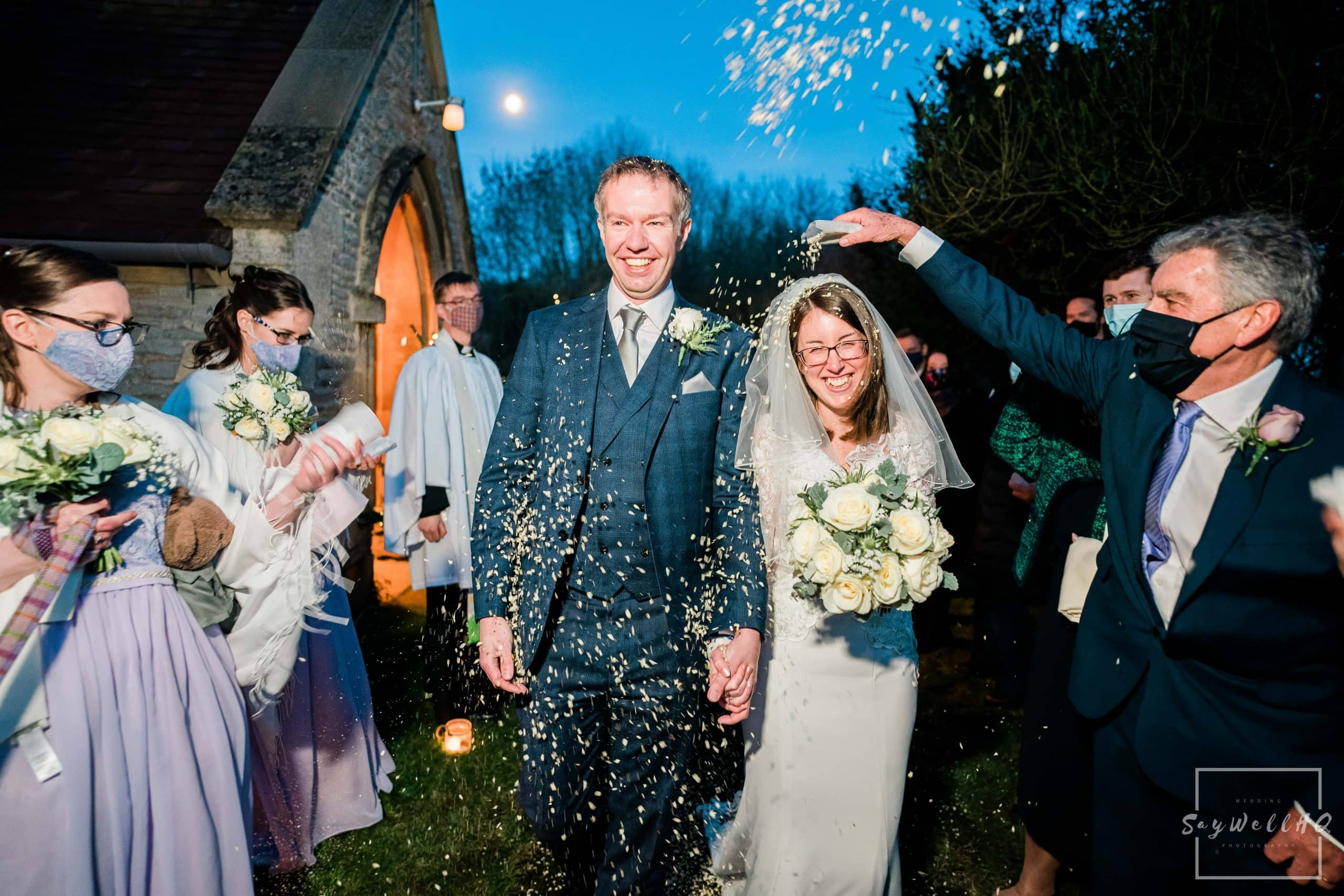 Bride and Groom getting covered in confetti when leaving their wedding ceremony at St. Helena Church in Thoroton - Vale of Belvoir wedding photography