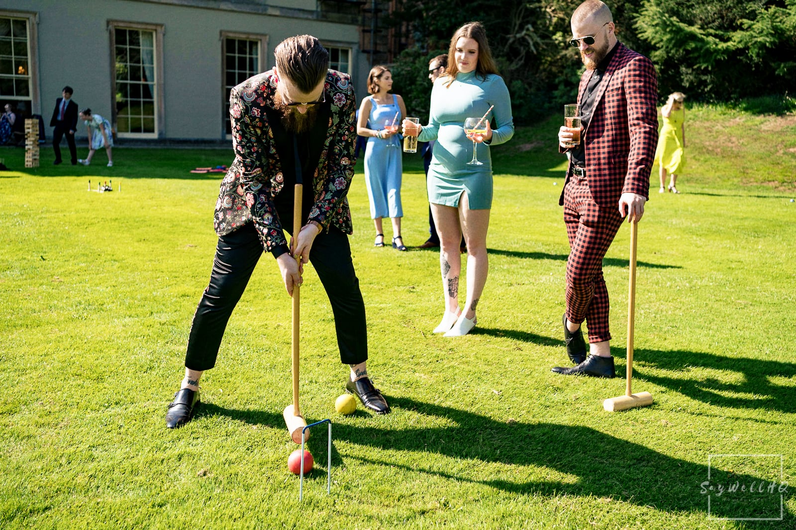 Prestwold Hall Wedding Photography - wedding guests enjoying the summer sunshine playing garden games in the grounds of Prestwold Hall