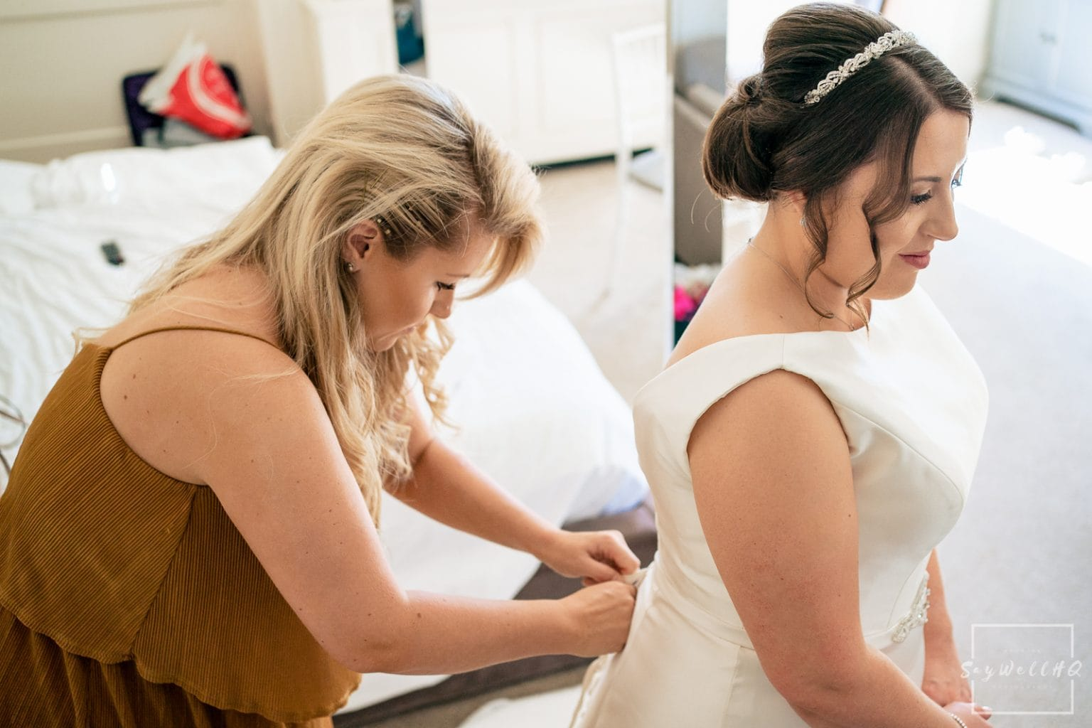 Winstanley House Wedding Photography - Bride gets into her wedding dress before the wedding