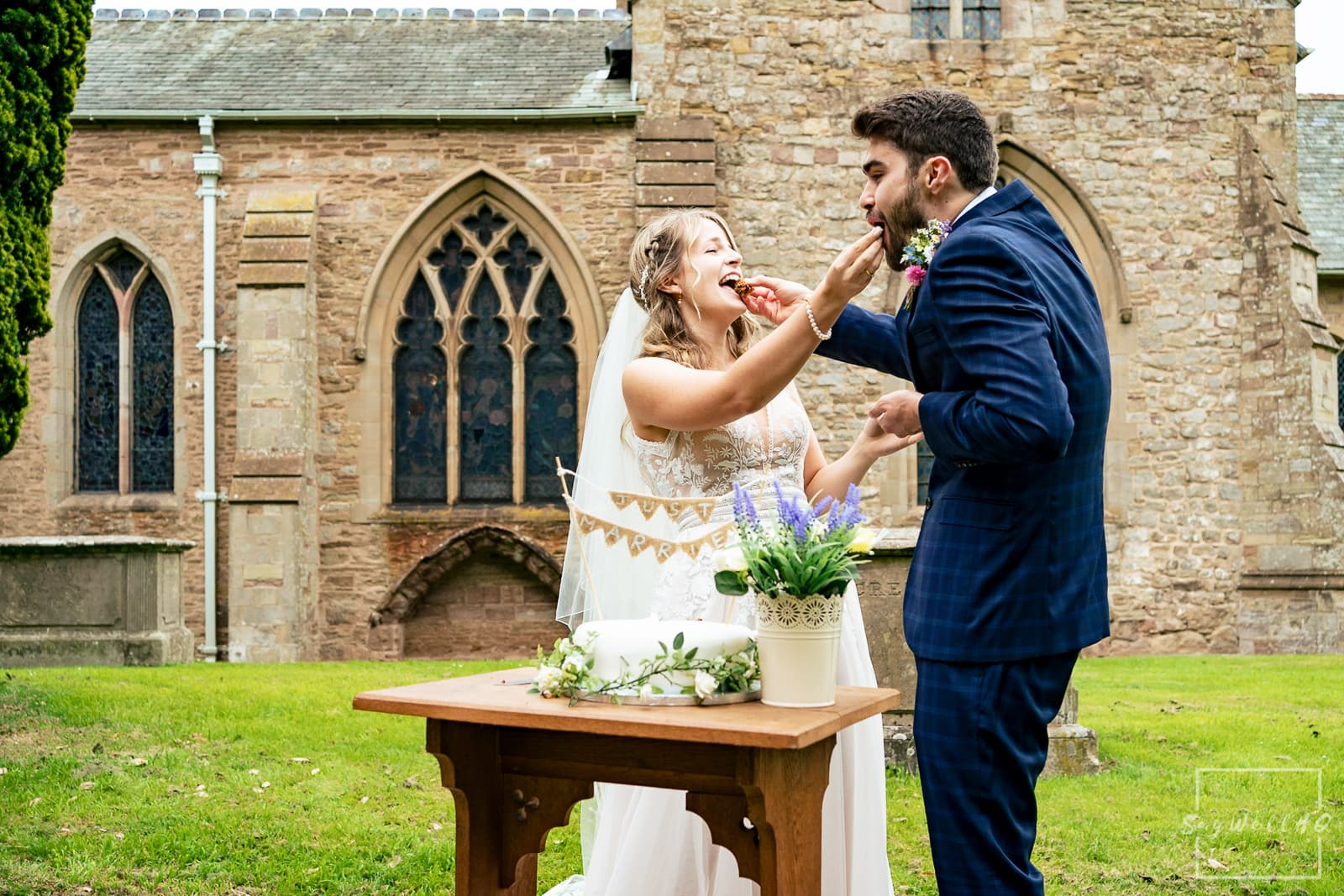 Hereford Church Wedding Photography - Bride and Groom cut the wedding cake in the grounds of the Church