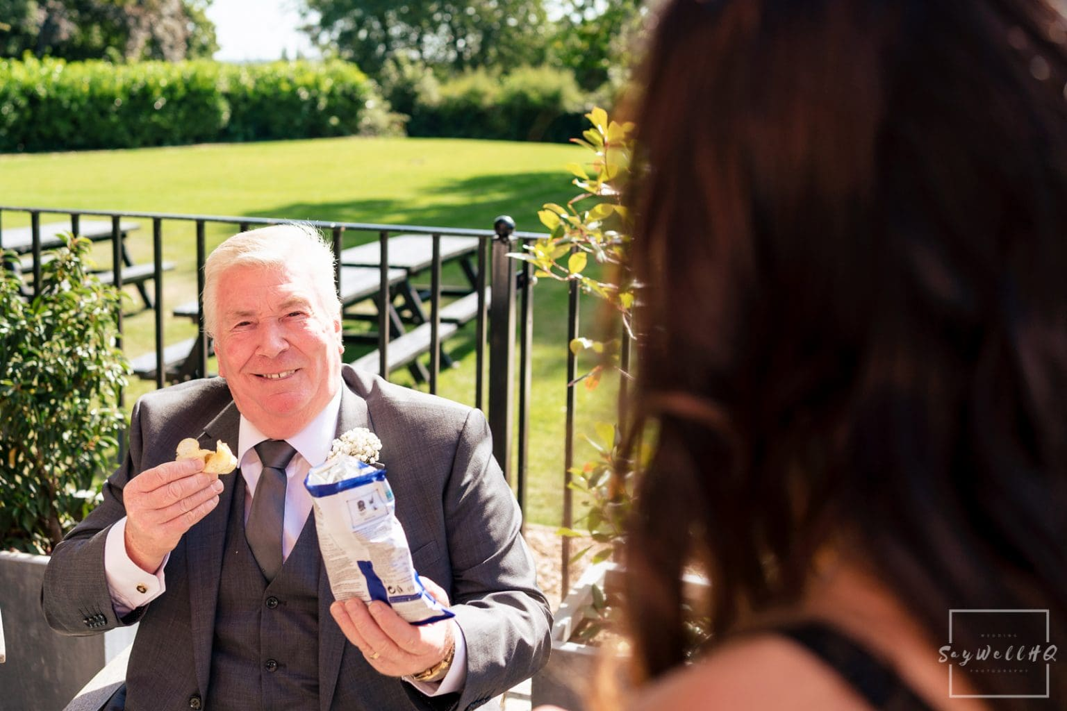 Winstanley House Wedding Photography - wedding guests settle down ready for the outdoor summer wedding