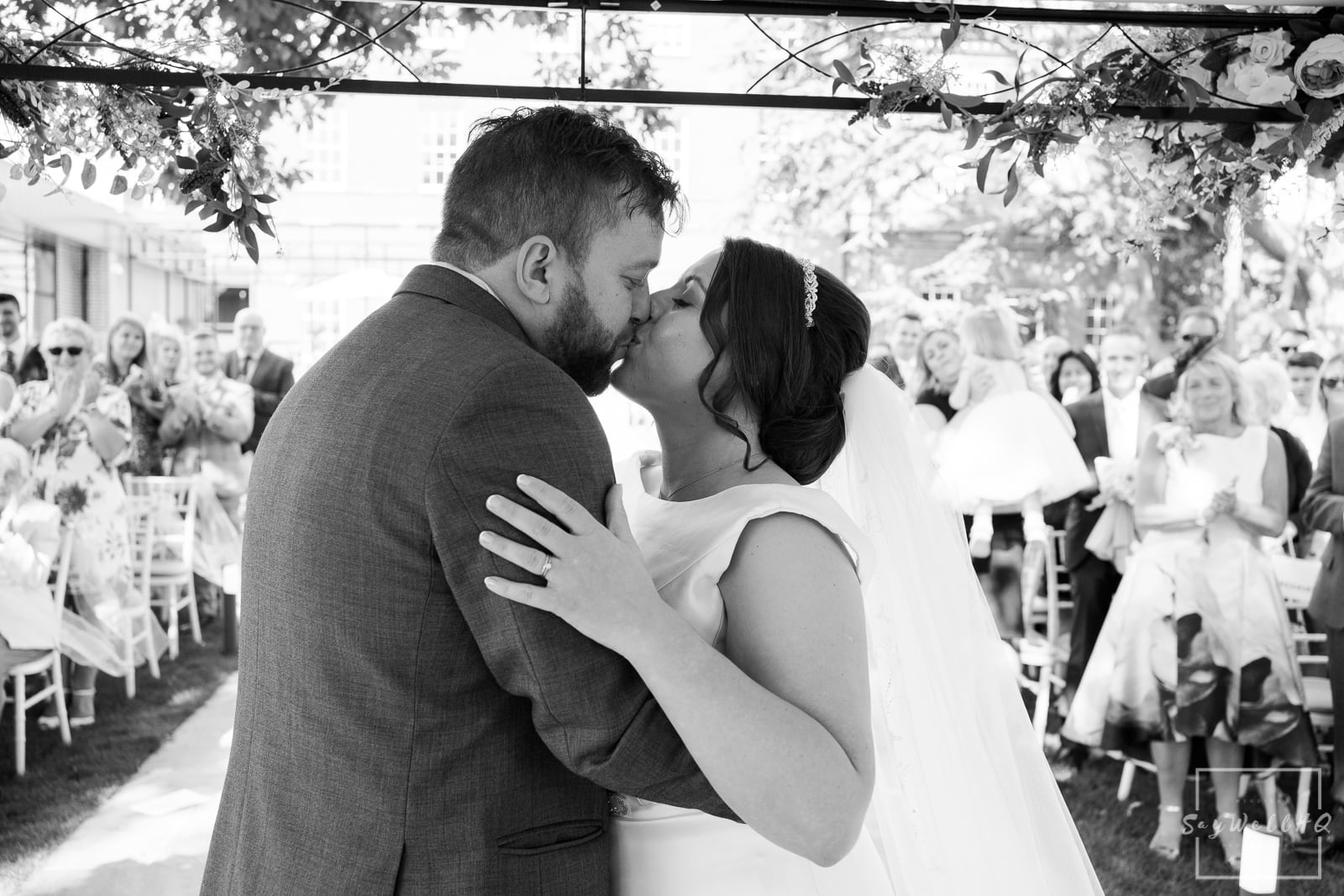 Winstanley House Wedding Photography - Bride and Groom first kiss after their outdoor summer wedding ceremony
