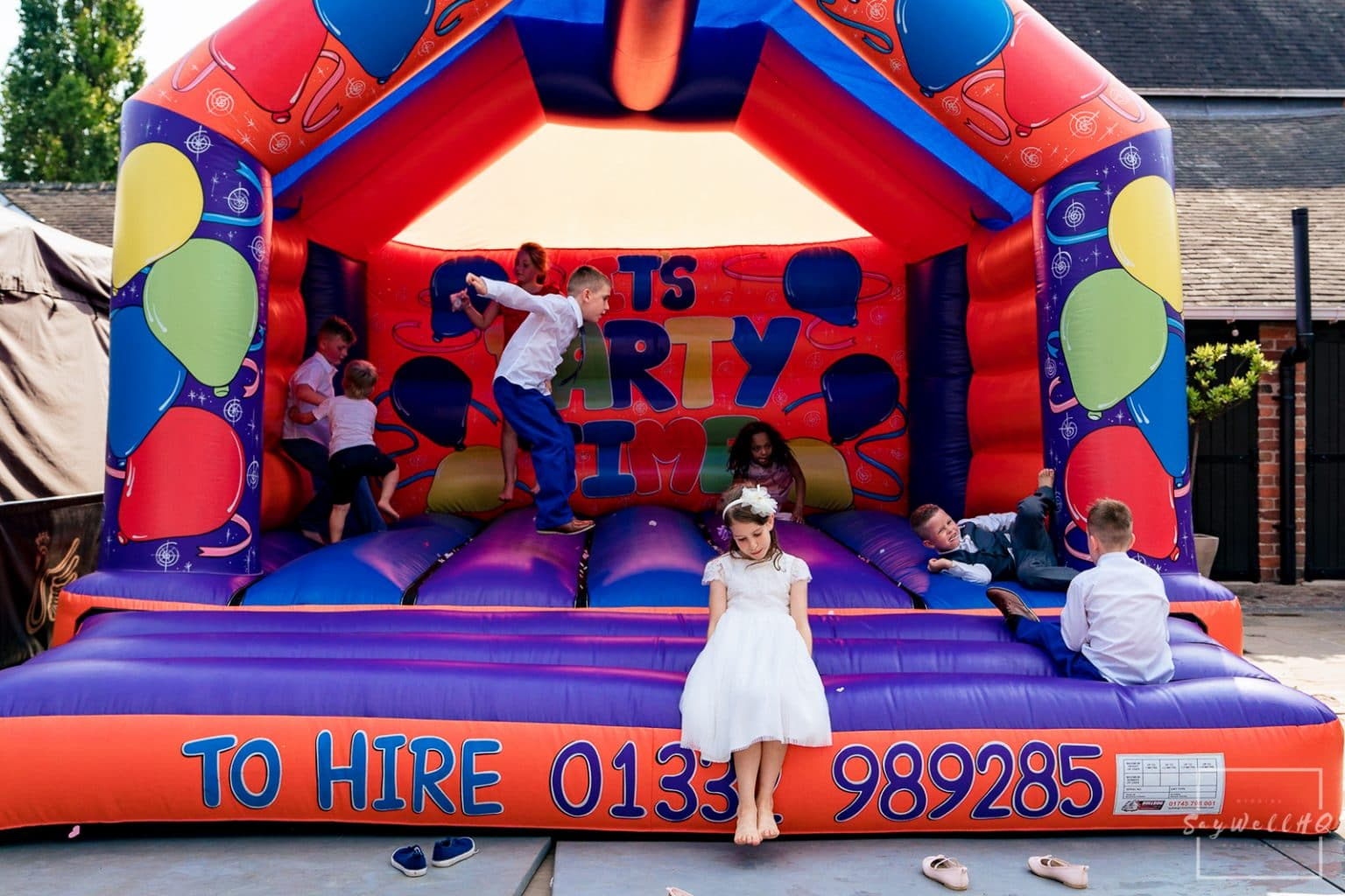 Swancar Farm Wedding Photography - wedding guests enjoy the bouncy castle at a wedding at Swancar Farm