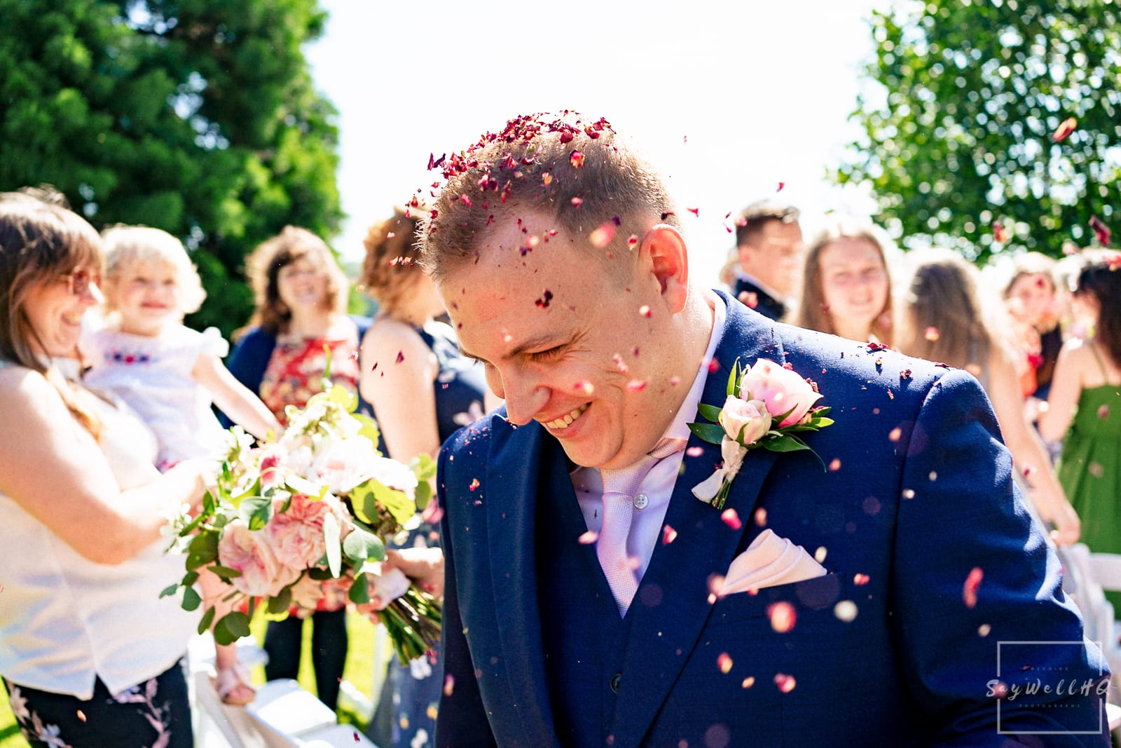 Prestwold Hall Wedding Photography - Bride and groom get covered in confetti after their outdoor wedding ceremony in the gardens at Prestwold Hall