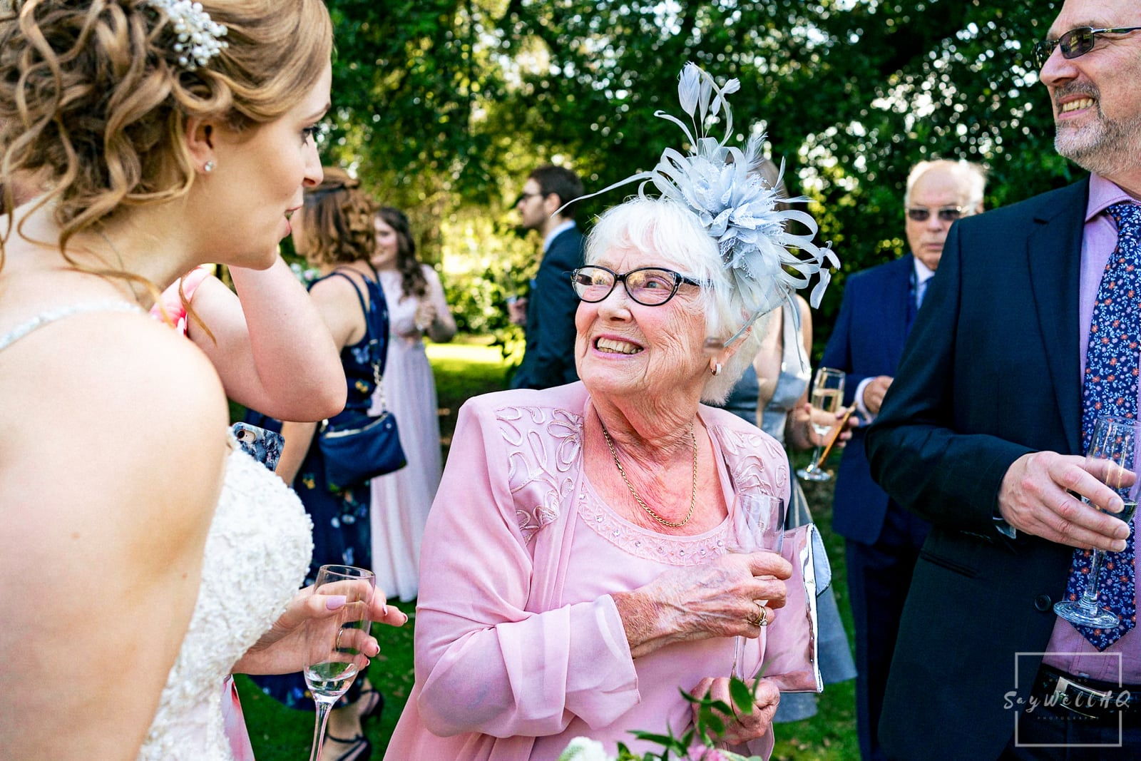 Prestwold Hall Wedding Photography - wedding guests enjoying the summer sunshine in the grounds of Prestwold Hall