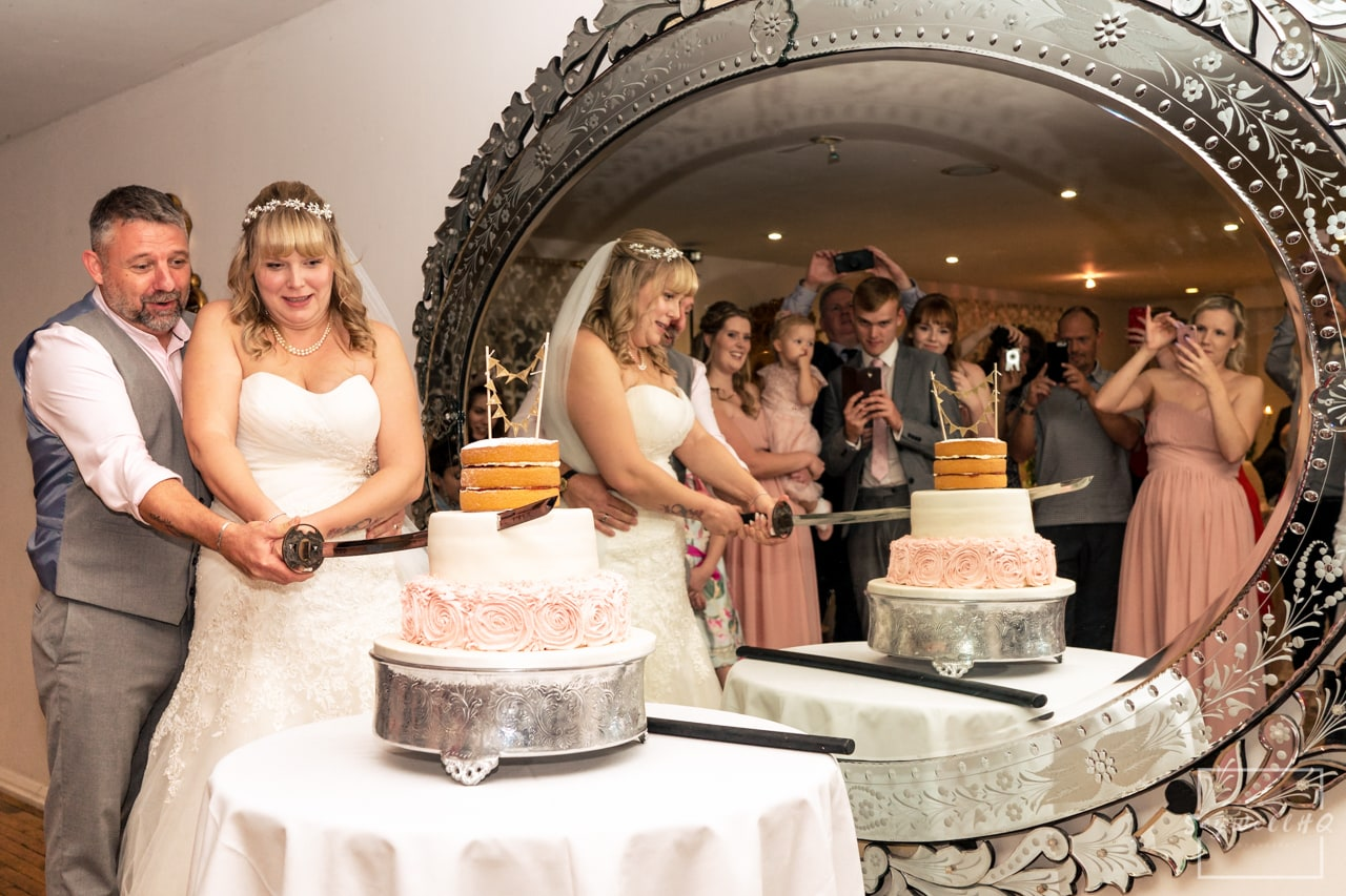 Woodborough Hall Wedding Photography + Bride and groom cutting the wedding cake in front of a big mirror