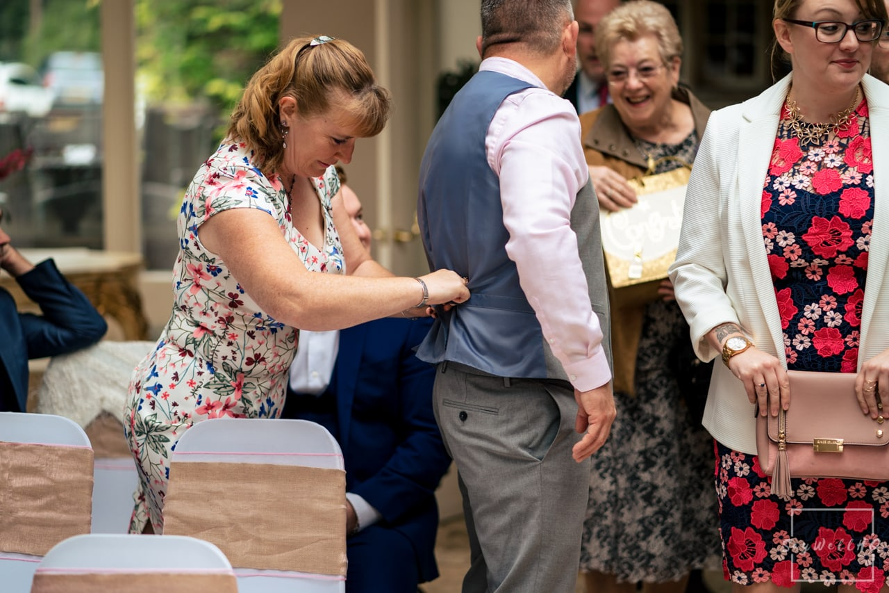 Woodborough Hall Wedding Photography + wedding guests take their seats in the wedding ceremony room