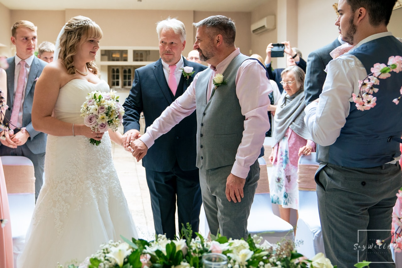 Woodborough Hall Wedding Photography + father of the bride handing overs his daughters hand to the groom