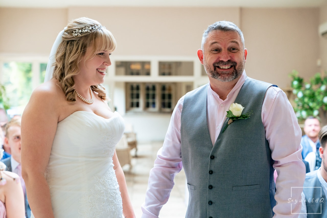 Woodborough Hall Wedding Photography + Bride and groom looking happy during the wedding ceremony