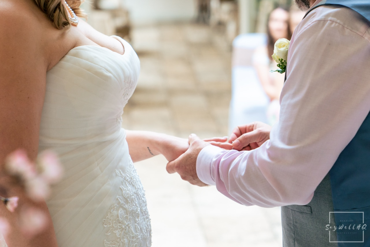 Woodborough Hall Wedding Photography + Bride and groom exchange rings during the wedding ceremony