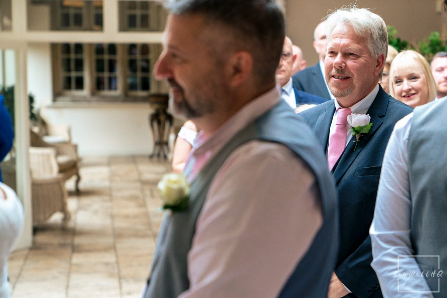 Woodborough Hall Wedding Photography + wedding ceremony wedding guests looking on as the bride and groom exchange rings