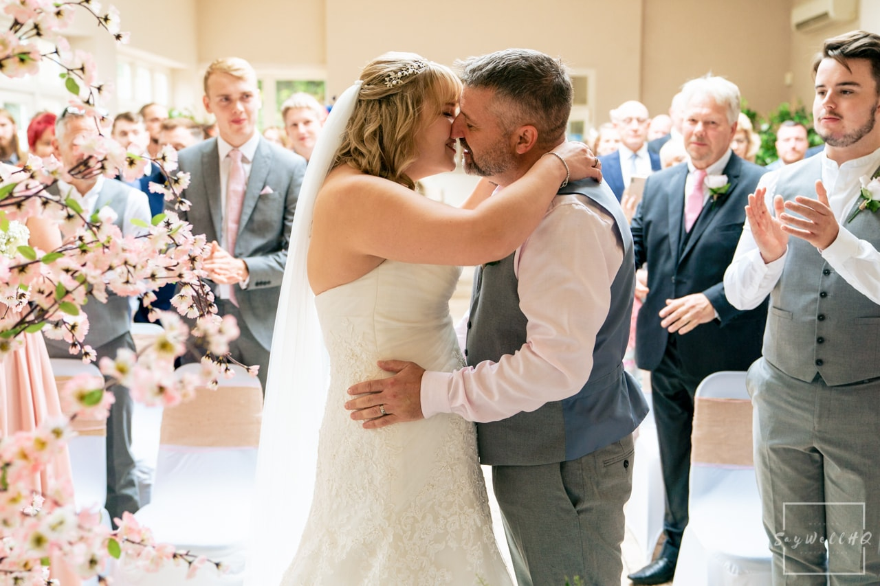 Woodborough Hall Wedding Photography + Bride and groom first kiss following their wedding vows