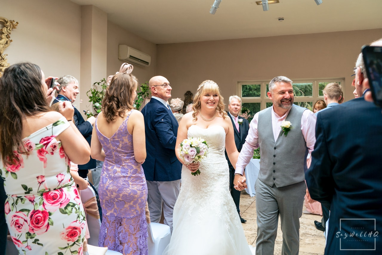 Woodborough Hall Wedding Photography + Bride and groom walking back down the aisle as man and wife