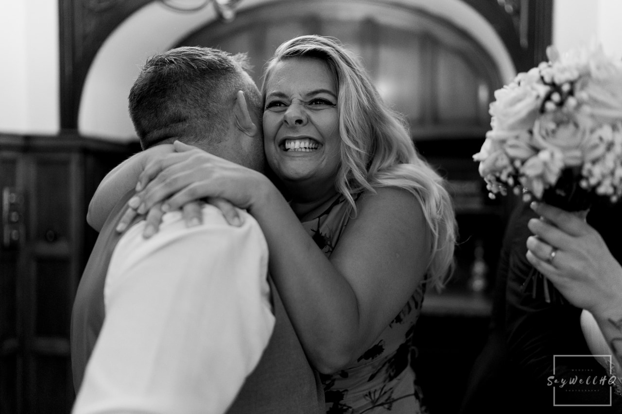 Woodborough Hall Wedding Photography + wedding guests hug and celebrate with the newly weds