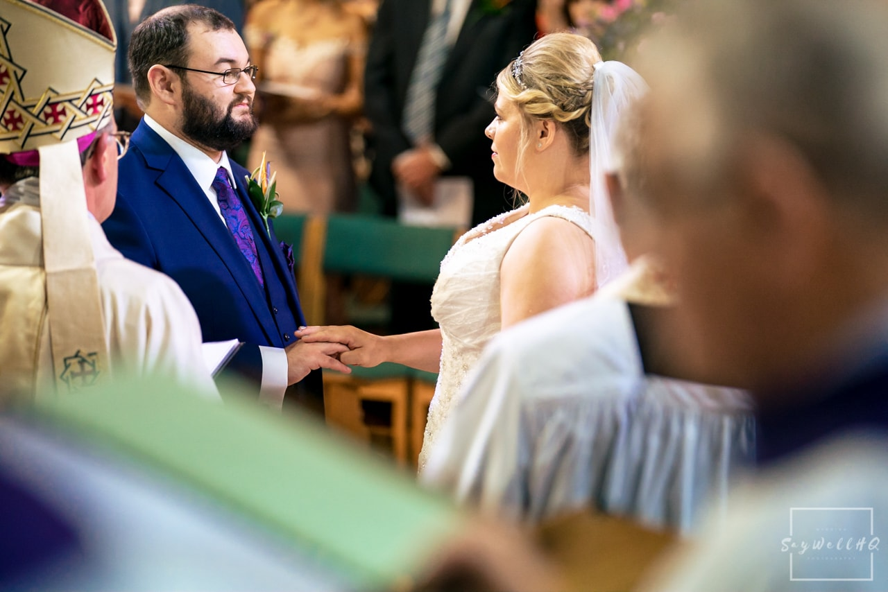 Derby wedding photographer - bride and groom looking at each other lovingly during the wedding ceremony