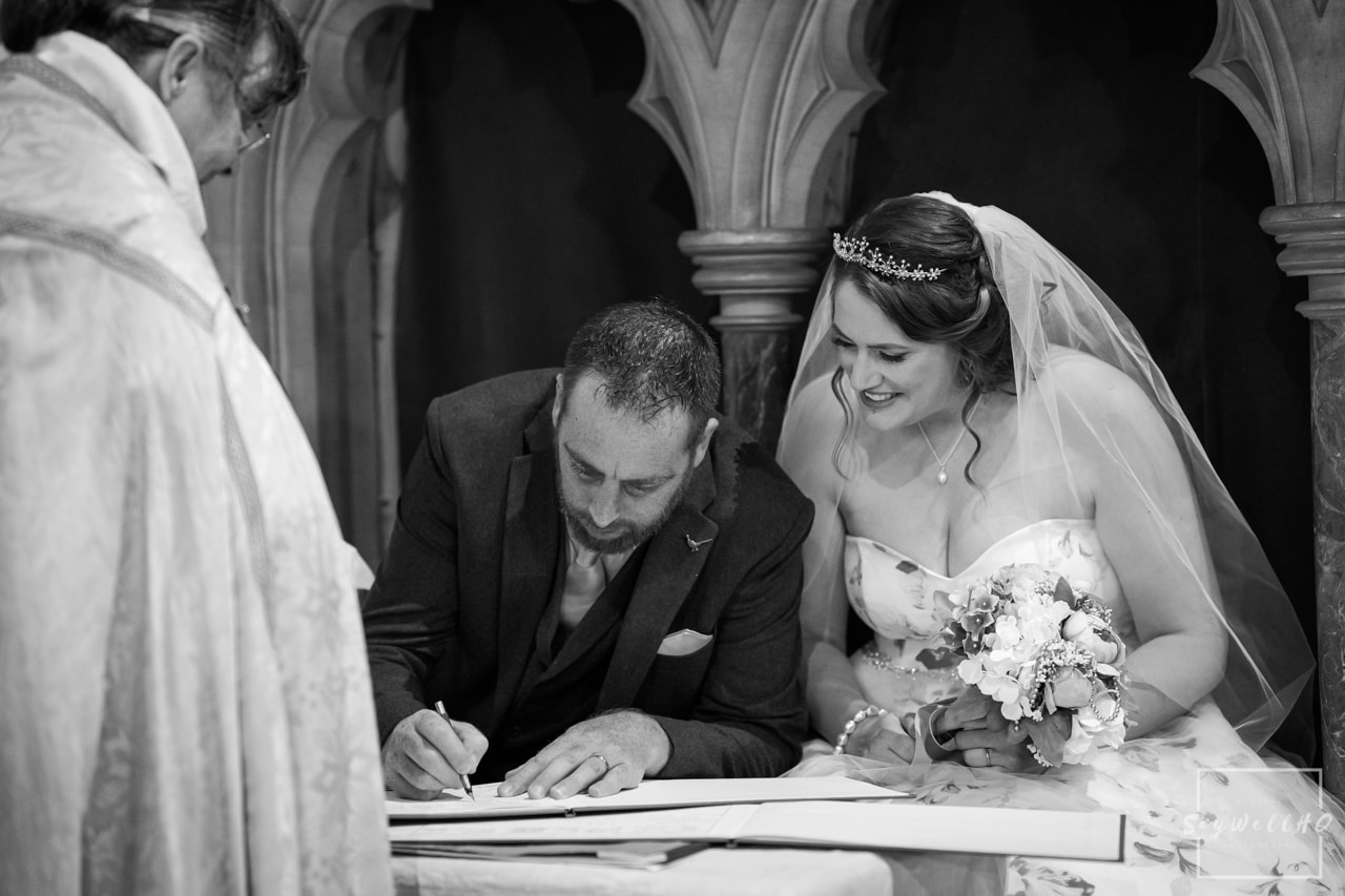 Wedding photography Signing the wedding register - The happy couple sign the wedding register in a candid and natural way