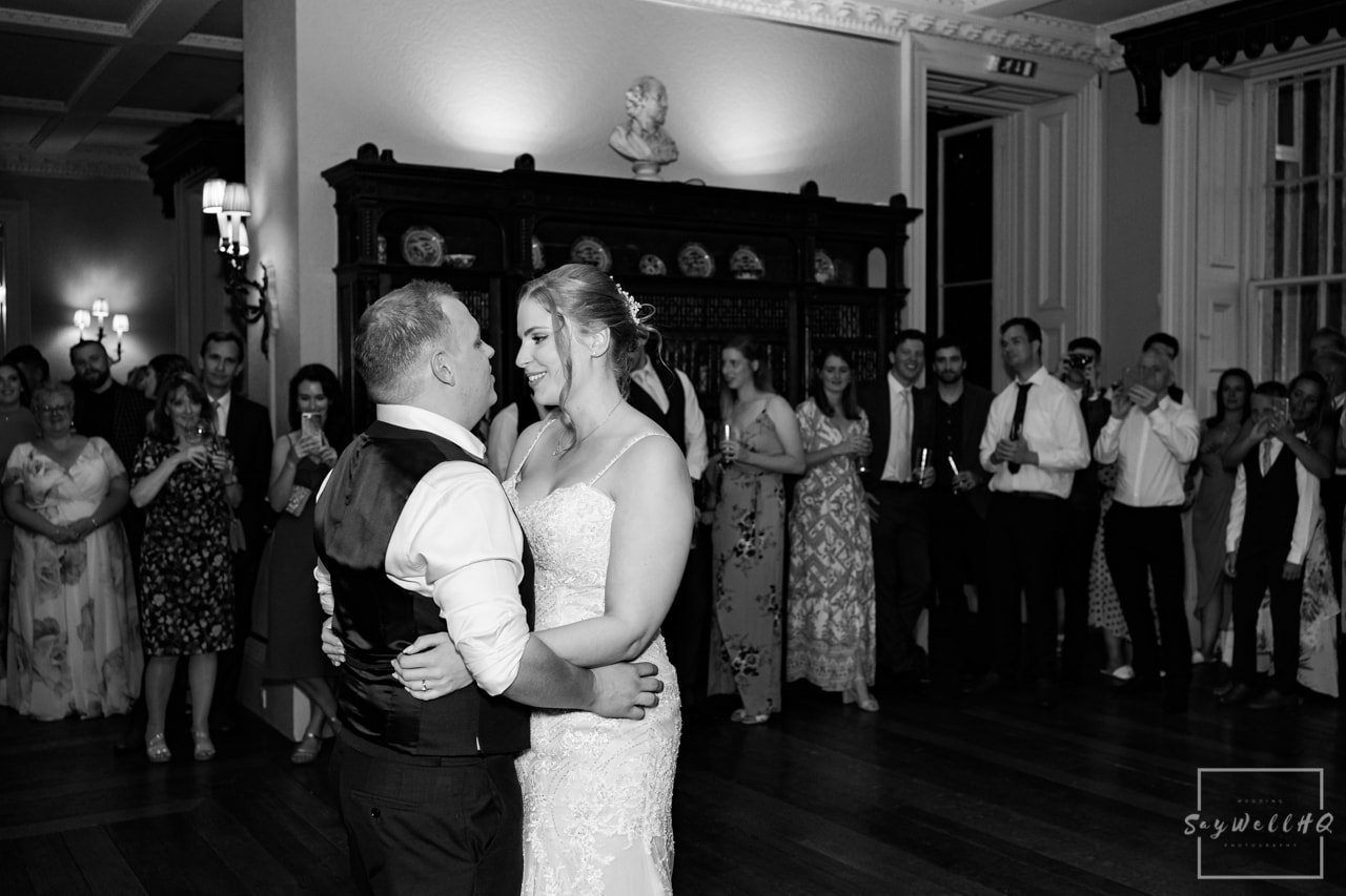 First dance wedding photography - bride and groom dance during their first dance with their wedding guests looking on