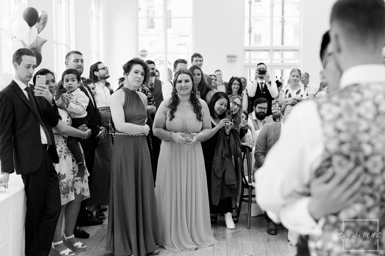 First dance wedding photography - wedding guests looking on as the happy couple dance during the wedding first dance