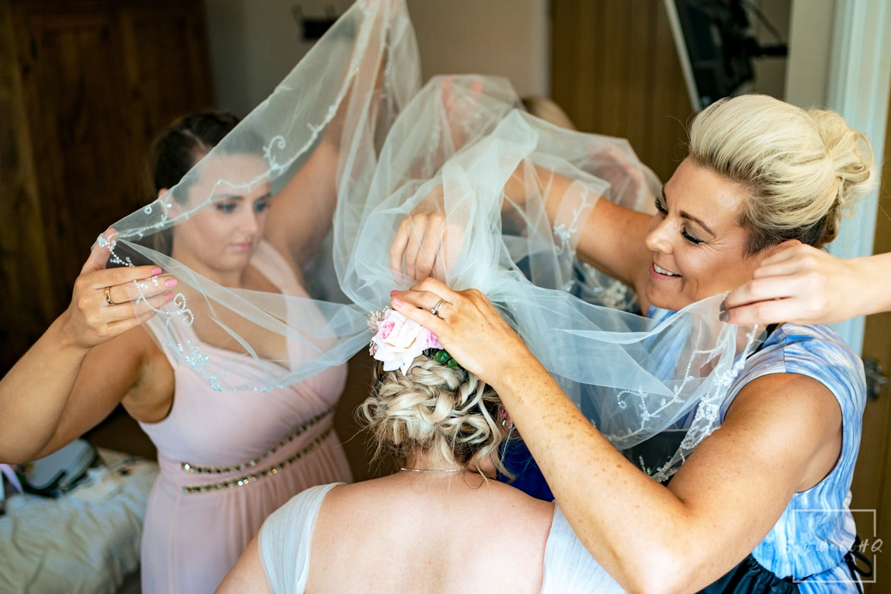 White Hart Inn Wedding Photographer - Bride and the Veil - everyone helping the bride getting the veil on - Derby Wedding Photography