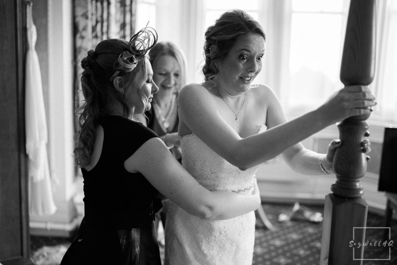 bestwood-lodge-wedding-photography-bride-getting-help-getting-in-to-her-wedding-dress-on-the-day-of-her-wedding