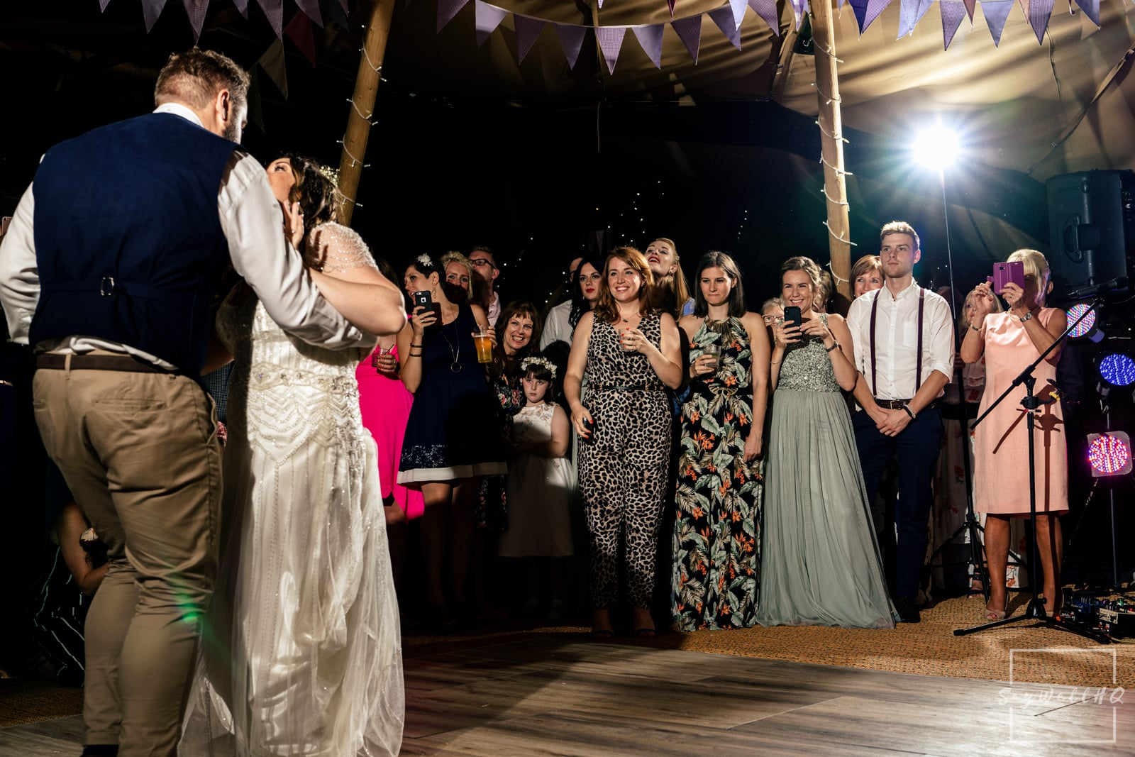 Mapperley Farm Wedding Photography + Mapperley Farm Wedding Photographer + wedding guests looking on as the bride and groom first dance inside their wedding tipi at an outdoor summer wedding