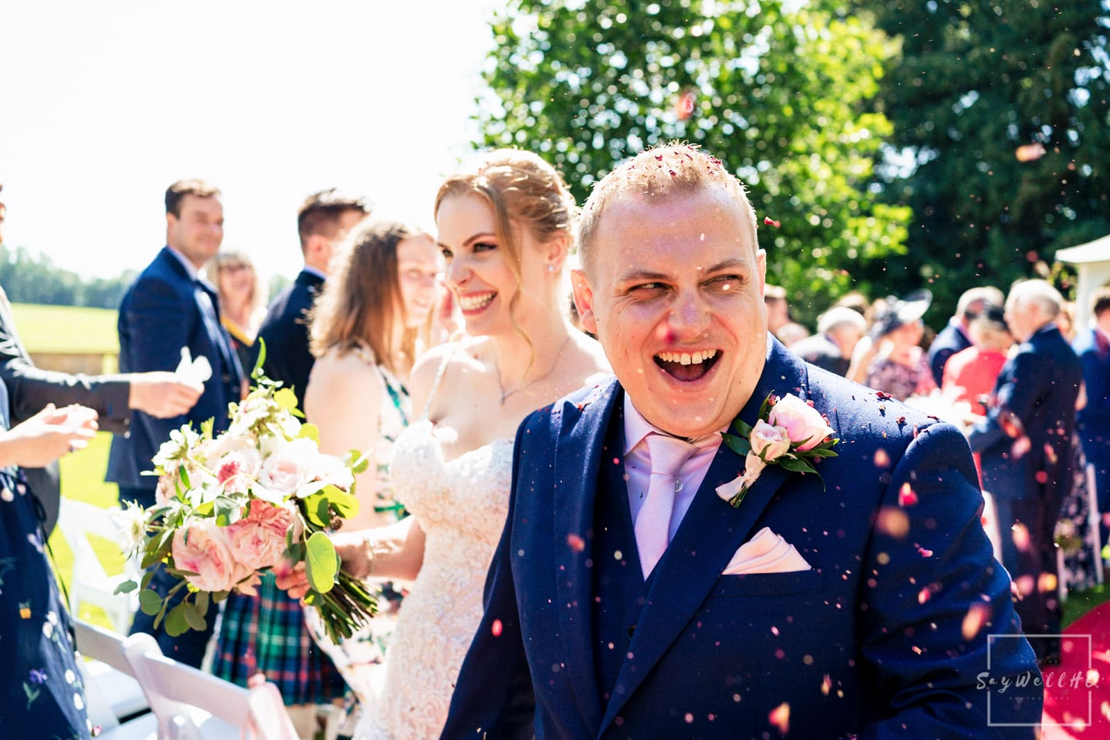 Prestwold Hall Wedding Photography + Bride and groom getting covered in confetti after their outdoor wedding ceremony