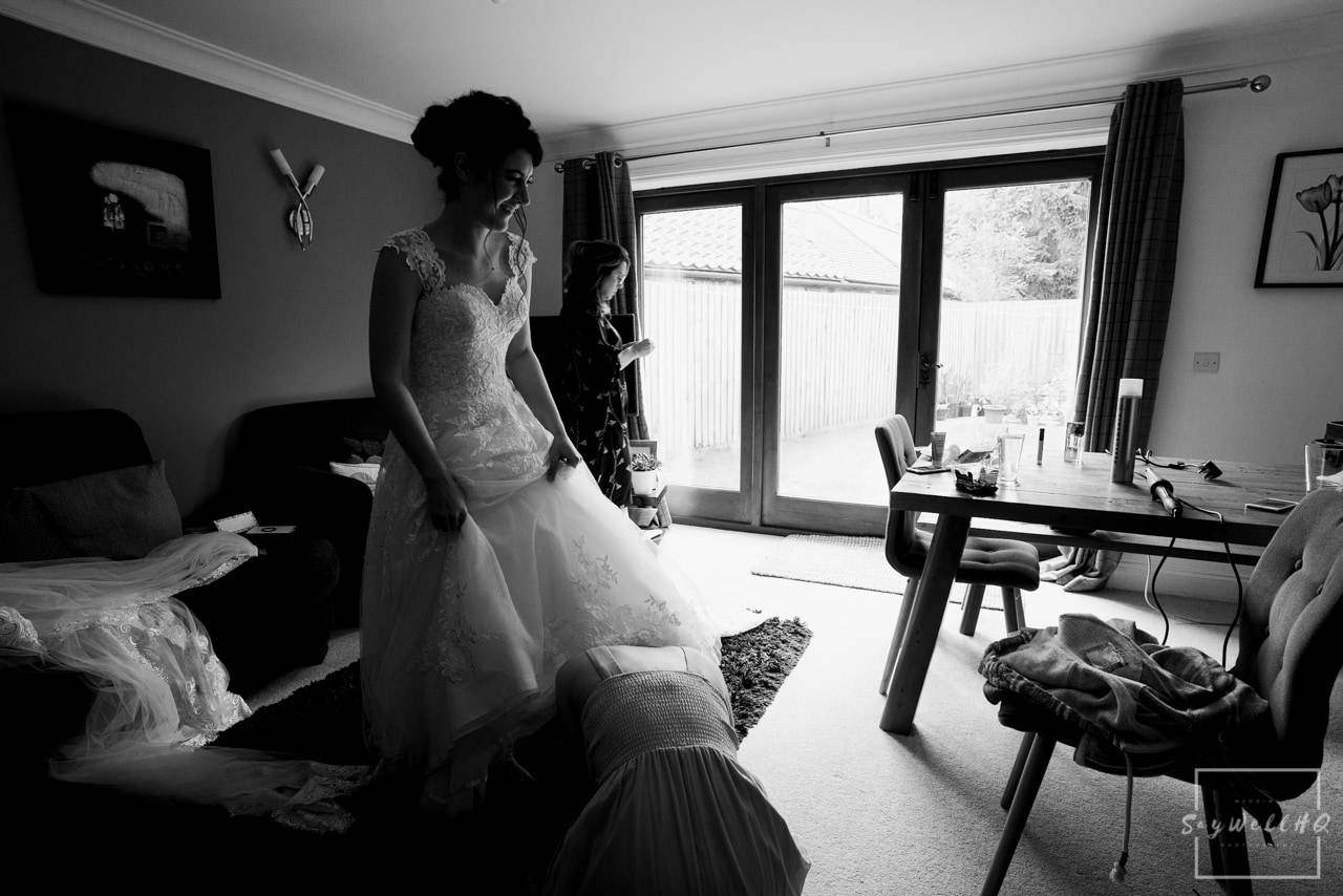 Southwell Wedding Photography + Newark Wedding Photographer + Church Wedding Photographer + bride getting help from her sister in getting into her wedding dress