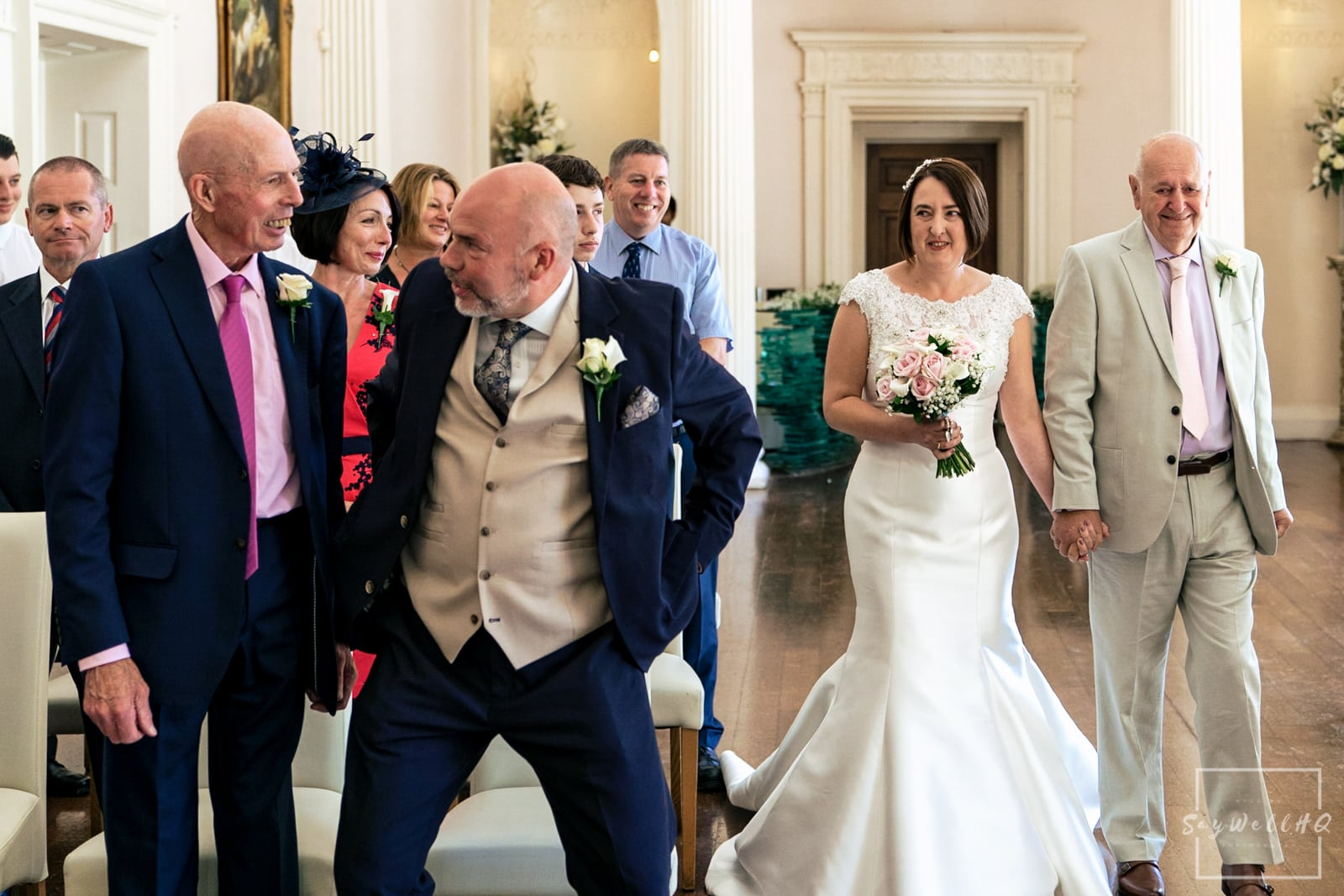 Colwick Hall Wedding Photography + Colwick Hall Wedding Photographer + groom adjusts his trousers just as the bride and her father start walking down the wedding aisle