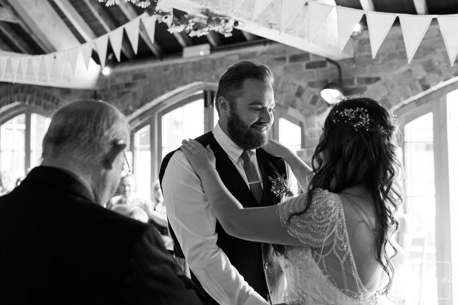 Bride and groom hold each other after their first kiss at their wedding at mapperley farm