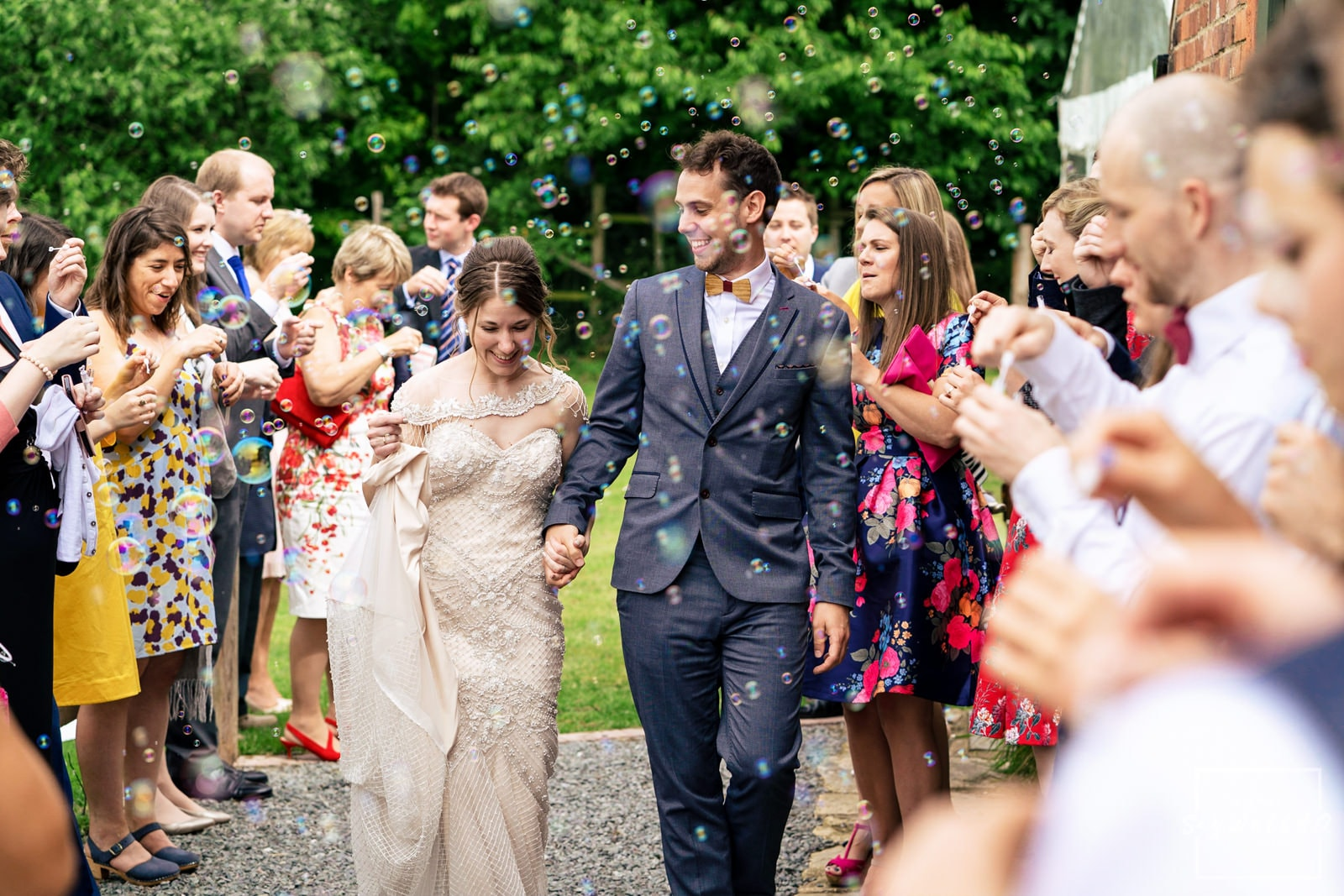 Leicester Wedding Photography + Leicester Wedding Photographer + Humanist Wedding Photographer + bride and groom walking through the confetti bubbles after their Humanist Wedding Ceremony