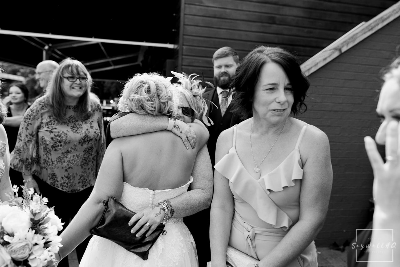 Brewhouse and Kitchen Wedding Photography + The Riverside Gallery Wedding Photographer + wedding guests celebrate with the bride and groom after the wedding ceremony