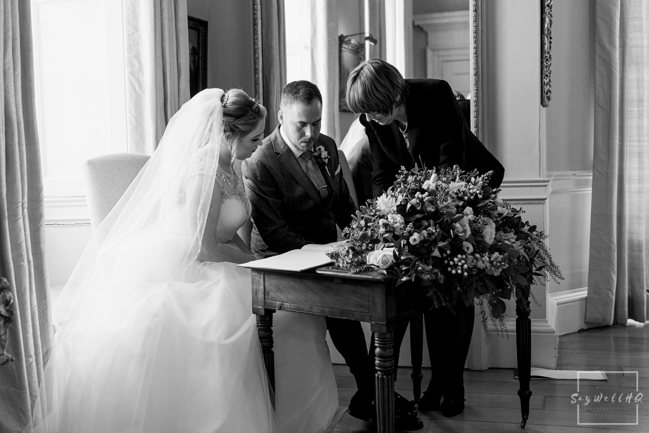 Norwood Park Wedding Photography + bride and groom sign the wedding register during their Norwood Park Wedding Ceremony