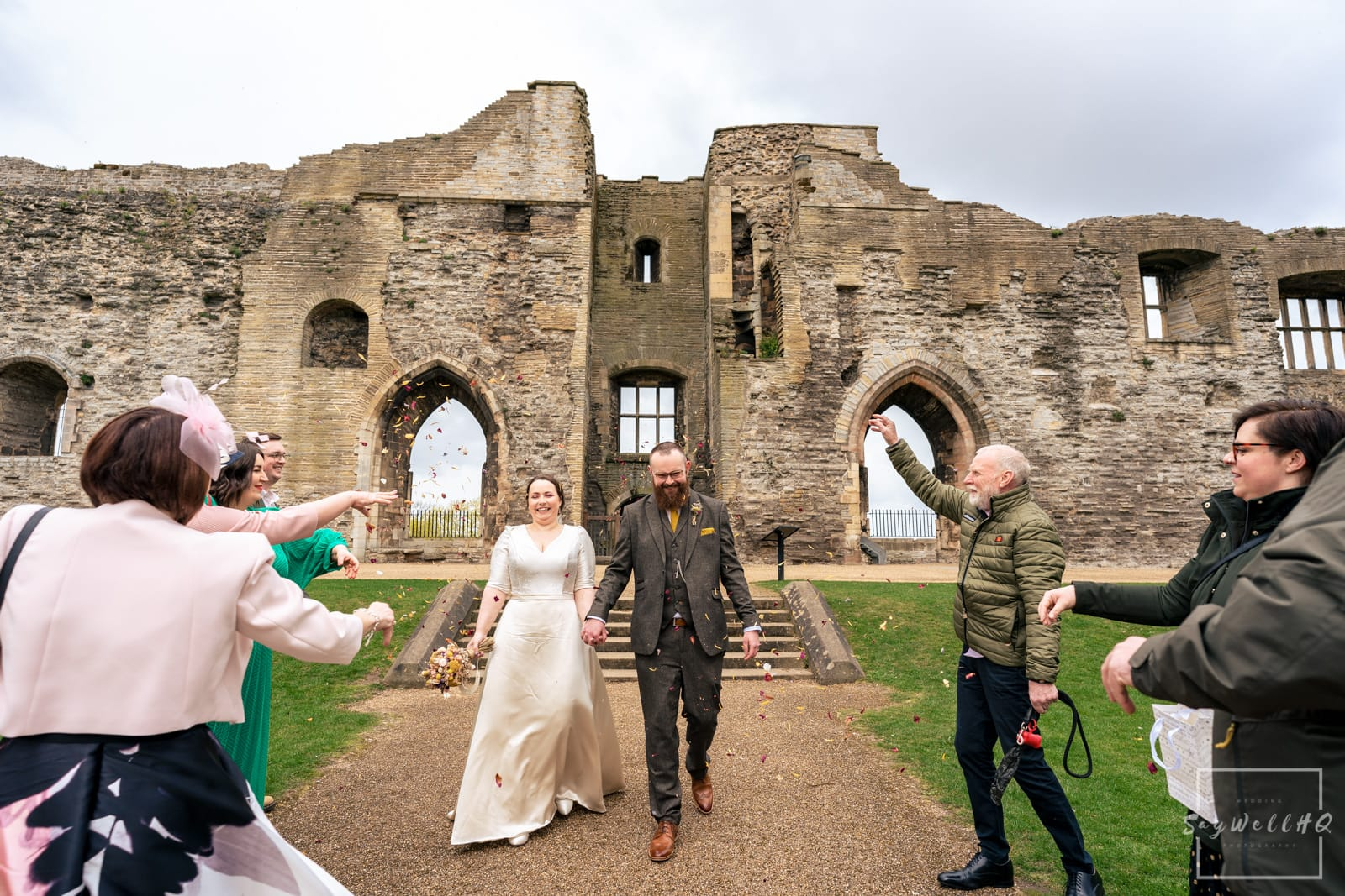 Newark Wedding Photography + Newark Wedding Photographer + wedding guests cover the bride and groom in confetti in the grounds of Newark Castle