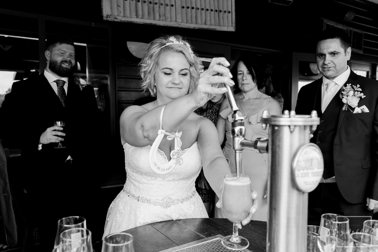 Brewhouse and Kitchen Wedding Photography + The Riverside Gallery Wedding Photographer + bride pours her own drink brewed especially for her wedding
