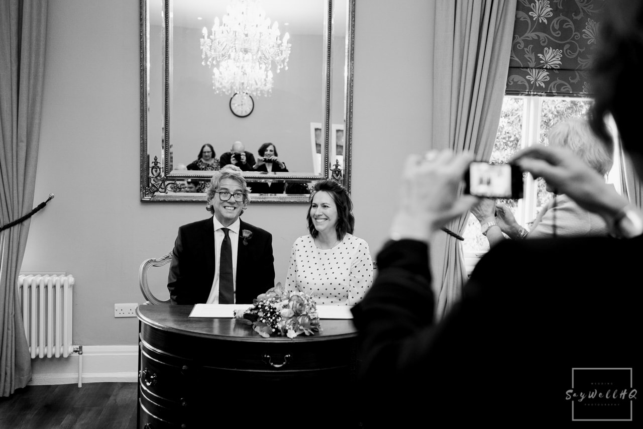 West Bridgford Hall Wedding Photography + Bridgford Hall Wedding Photographer + bride and groom smile for guest photos during the signing of the register pictures