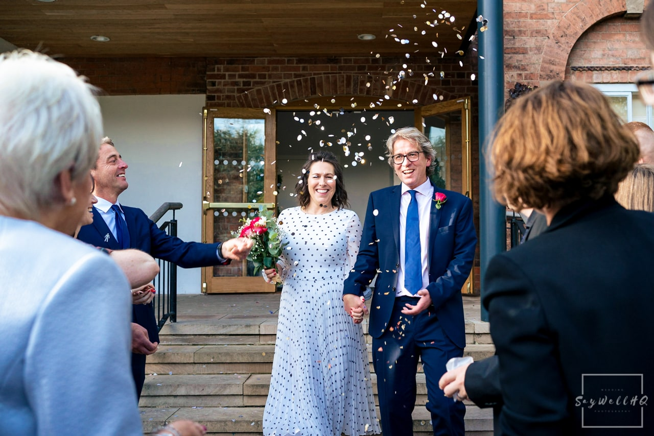 West Bridgford Hall Wedding Photography + Bridgford Hall Wedding Photographer + bride and groom get covered in confetti following their civil wedding ceremony
