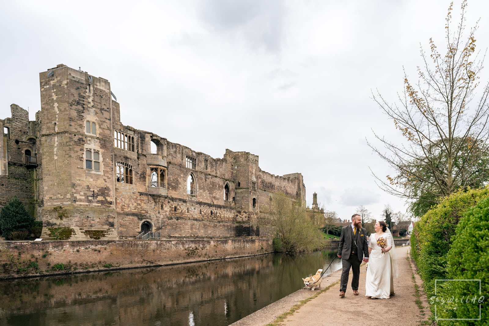 Newark Wedding Photography + Newark Wedding Photographer + Bride and Groom walking along the river Trent with Newark castle over the water