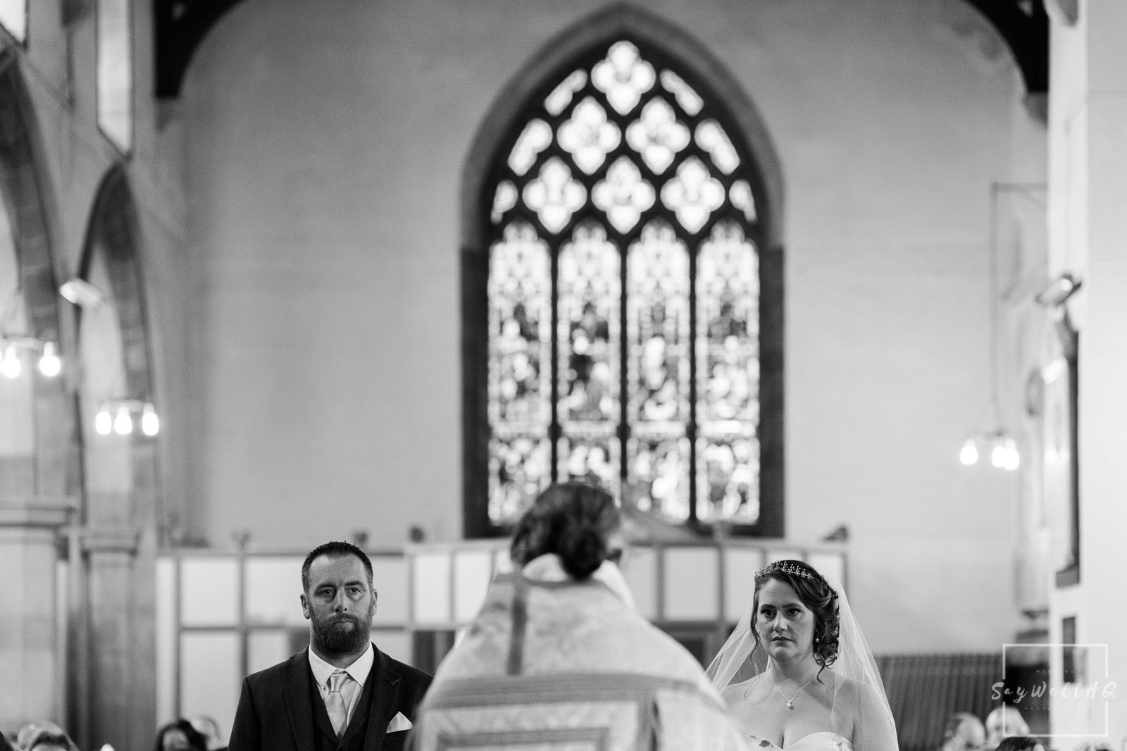 Lincoln wedding photographer -bride and groom during the wedding ceremony listen to instructions from the Vicar