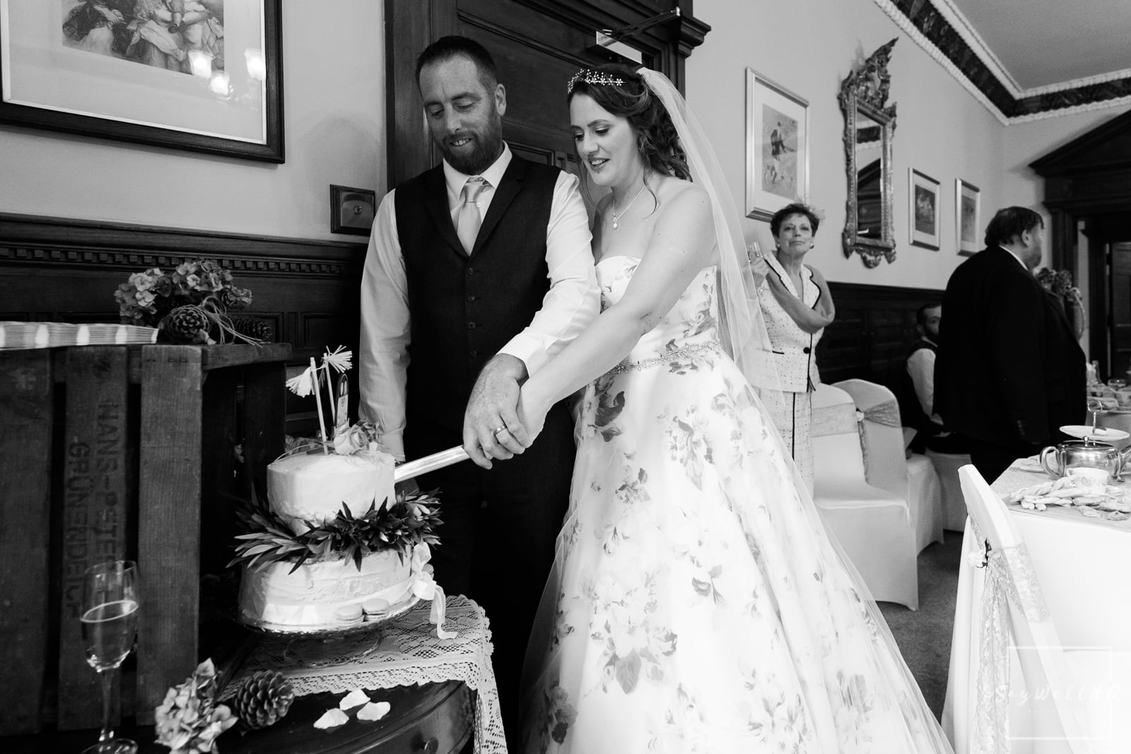 Lincoln Wedding Photography + Spilsby Church Wedding Photographer + bride and groom cut their wedding cake at Skendleby Hall